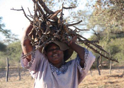 Frau traegt Feuerholz auf dem Kopf